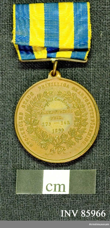 """Grupp M. Åtidan: Lika med nr: 16267. Frånsidan: Lika med nr: 16267, dock med den skilnad att under ordet """"målskjutningspris"""" är ingraverat: 279-262 1899 på 2 rader. Medaljen är försedd med bandhållare, bandet vattrat rips med 3 blå och 2 gula lodräta ränder."""
