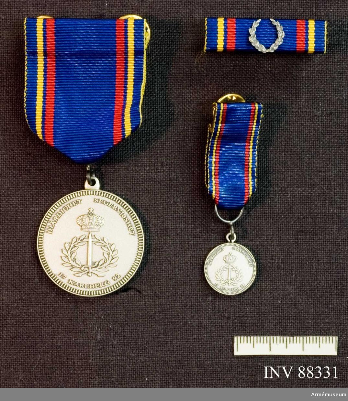 Tre samhörande föremål; en medalj, en minatyrmedalj och ett släpspänne. Bandet blått med en gul och en röd rand på vardera sidan..