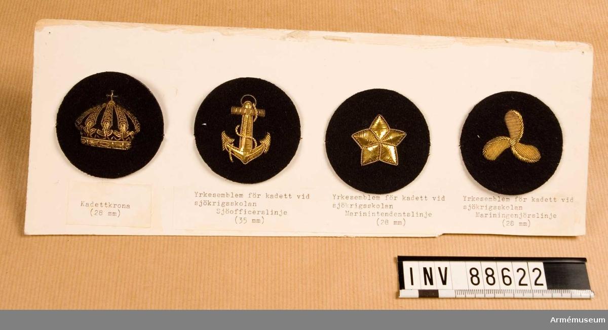 Fyra tygmärken: kadettkrona, kadett vid sjöofficerslinjen, kadett vid marin-intendentslinjen, kadett vid mariningenjörslinjen.