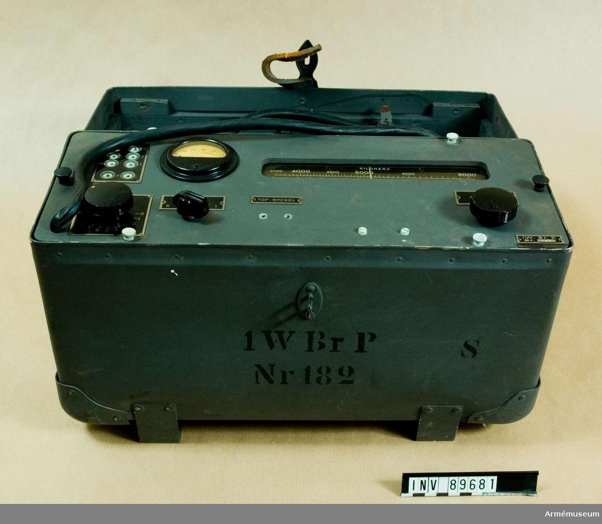 """Sändarlåda med sändarapparat. Märkt: 1 W Br P Nr. 182 (S). Antennvinda, antennlina, motviktslina, skruvmejsel och spetsstång saknas. Sändaren är uppbyggd på ett plåtchassi med frontplattan av """"masonite"""" och insatt i en låda av vulcanfiber """"unica"""", lådan är försedd med handtag och för bärning i mes. Mått: 420 x 263 x 175 mm."""