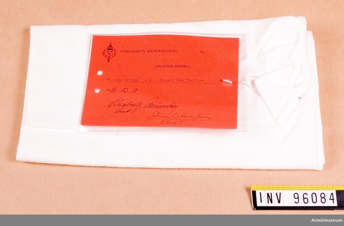 """Vidhängande etikett med text: """"Försvarets materielverk, Originalmodell, M7310-031000-5, Örngott Bom 55x65, 1986-02-18 Elisabeth Rönnberg IntT, Göran Olmarker QIntT"""""""