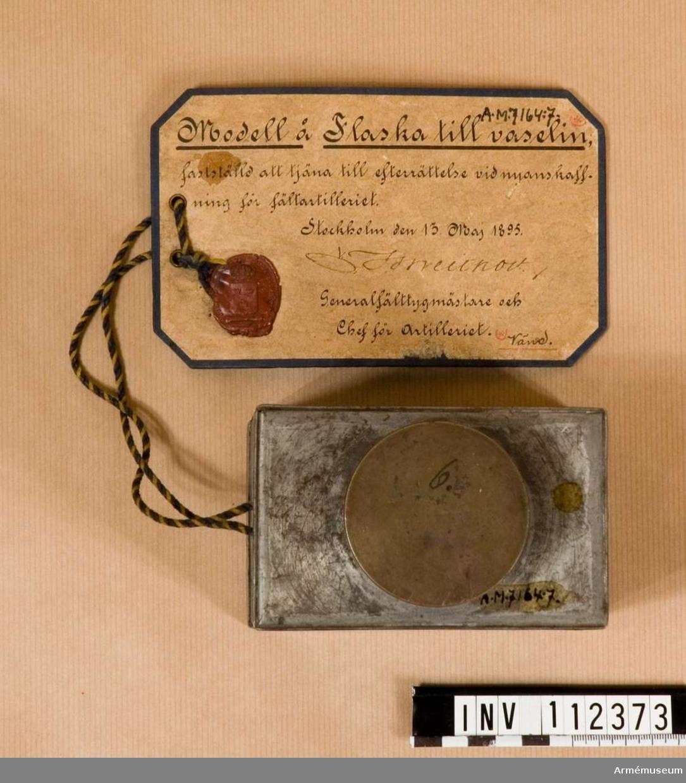 """Med tillhörande pensel. """"Modell å Flaska till vaselin, fastställd att tjäna till efterrättelse vid nyanskaffning för fältartilleriet. Stockholm den 13 Maj 1895."""" Till 8,4 cm kanon m/1881."""