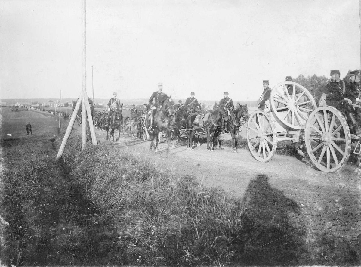 Kronprins Gustav (Gustav V) rider förbi en marschkolon med artillerister till häst, möjligen Vaxholms artillerikår A 8, under en manöver i Närke 1895.