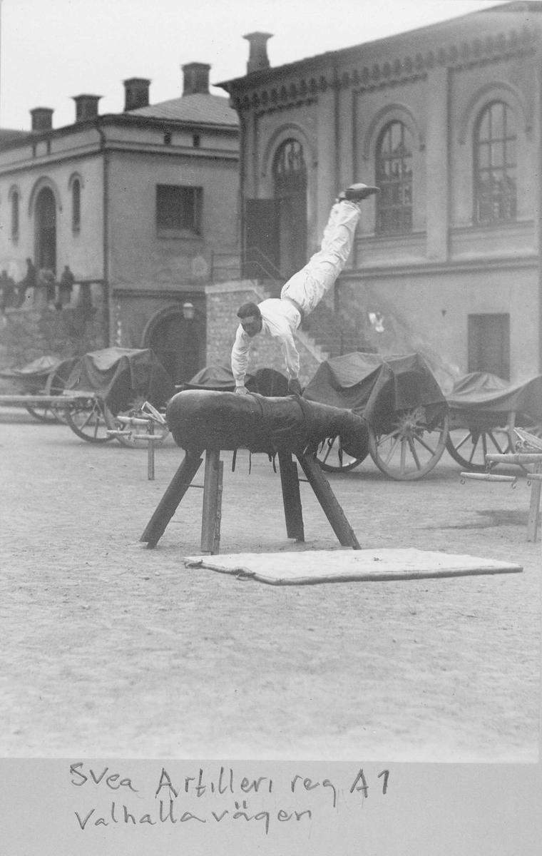 Gymnastik hos Svea artilleriregemente A 1 på Valhallavägen. Vitklädd man hoppar bock på kaserngården.  I bakgrunden artilleripjäser.