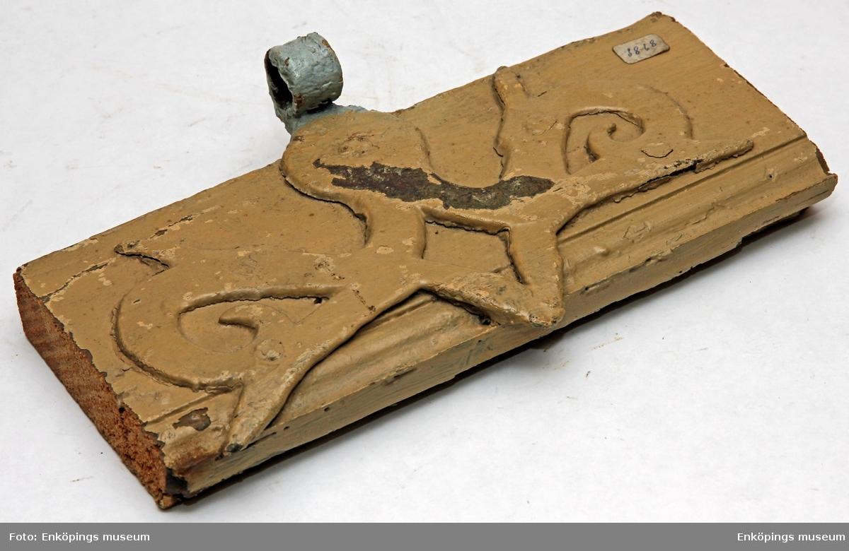 Gångjärn till dörr sittande på en bit trä. Målad med en färg som idag ser beige ut (terra).  På föremålets baksida finns en handskriven anteckning som säger Munksundsgatan 4.