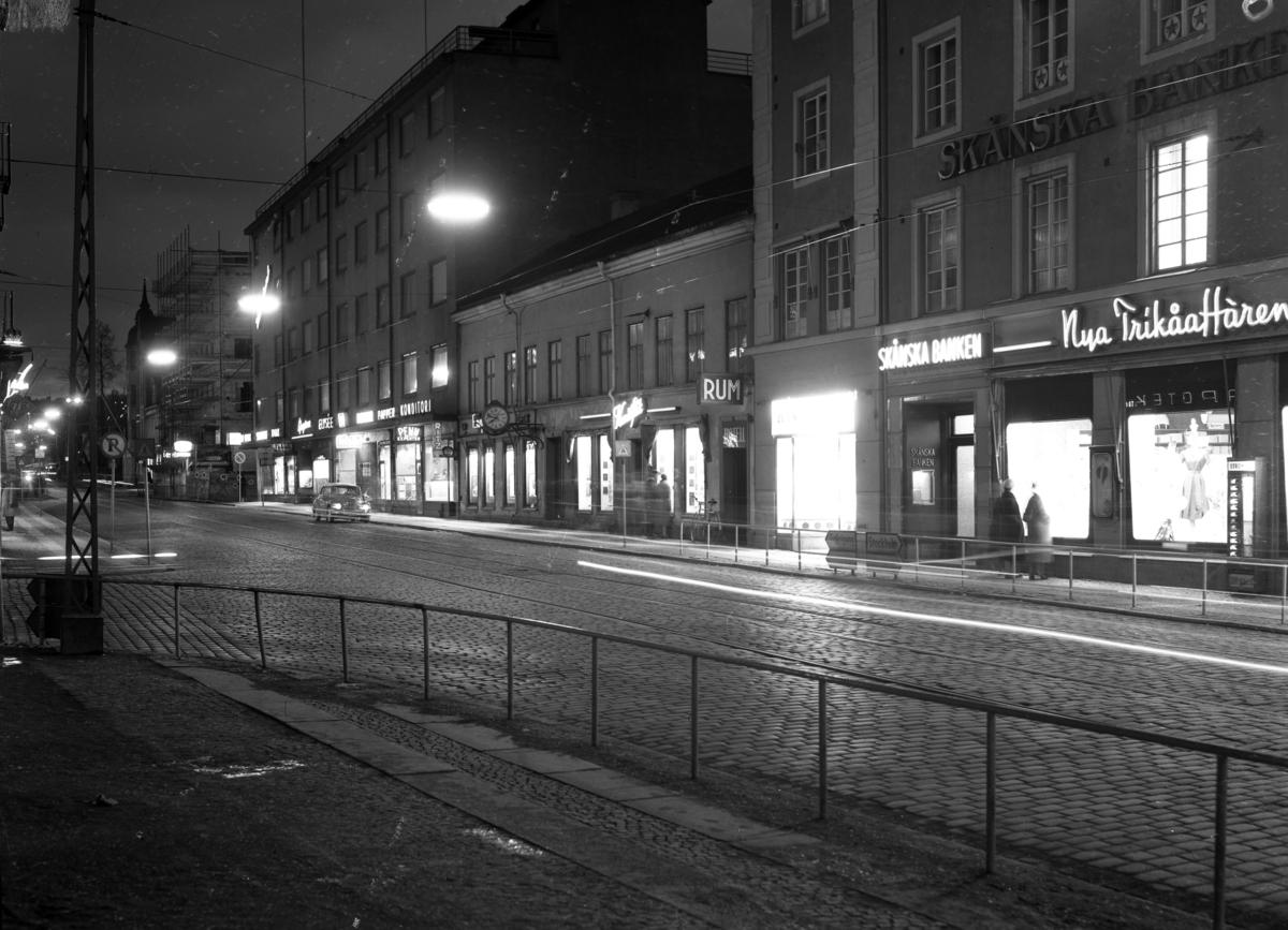 Neonskyltarna lyser upp Västra Storgatan i Jönköping den 9 april 1958.Till vänster Västerhuset och i mitten Västra Storgatan 4 med Engströms Ur och Konstflit. Till vänster om Skånska banken ligger en nyöppnad butik med namnet Handskcentrum. Till höger om Skånska bankens ingång ligger Nya Trikåaffären som hade en automat på fasaden för den som behövde köpa strumpor när butiken var stängd.
