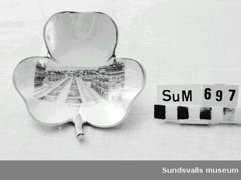 Treklöverformat askfat i porslin med tryckt motiv från Sundsvall. Guldfärgad stämpel i botten 'Import'.