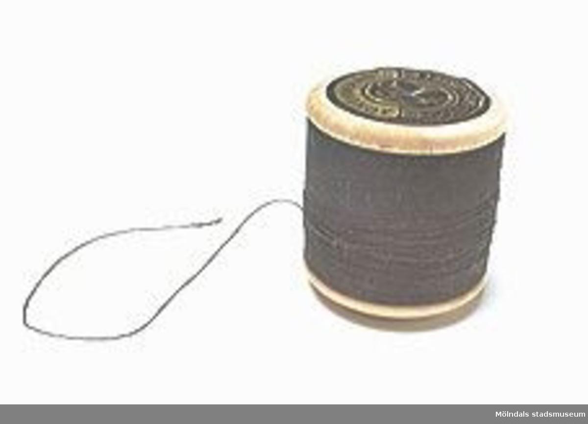 Trådrulle med svart tråd. Föga eller intet av tråden har använts. Märket på ovansidan är ej genombrutet. Märkt på etiketten med två korslagda nycklar.Den profilerade undersidan saknar märkning.