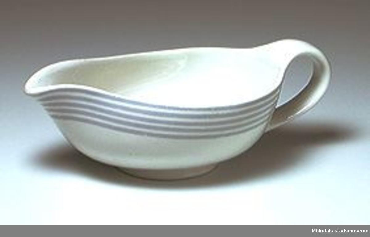 Såskanna i vitt  Wedgewoodporslin med handtag och pip. Dekor: 5 smala ljusgrå ränder runtom och parallellt med övre kanten. Design: Wilhelm Kåge.