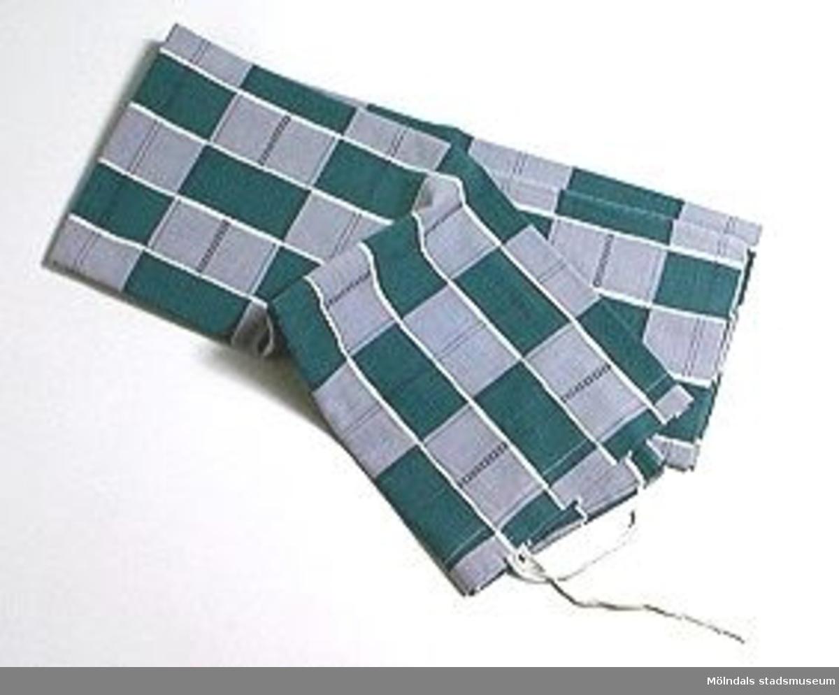 Påslakan i grå- och grönblårutigt tyg.
