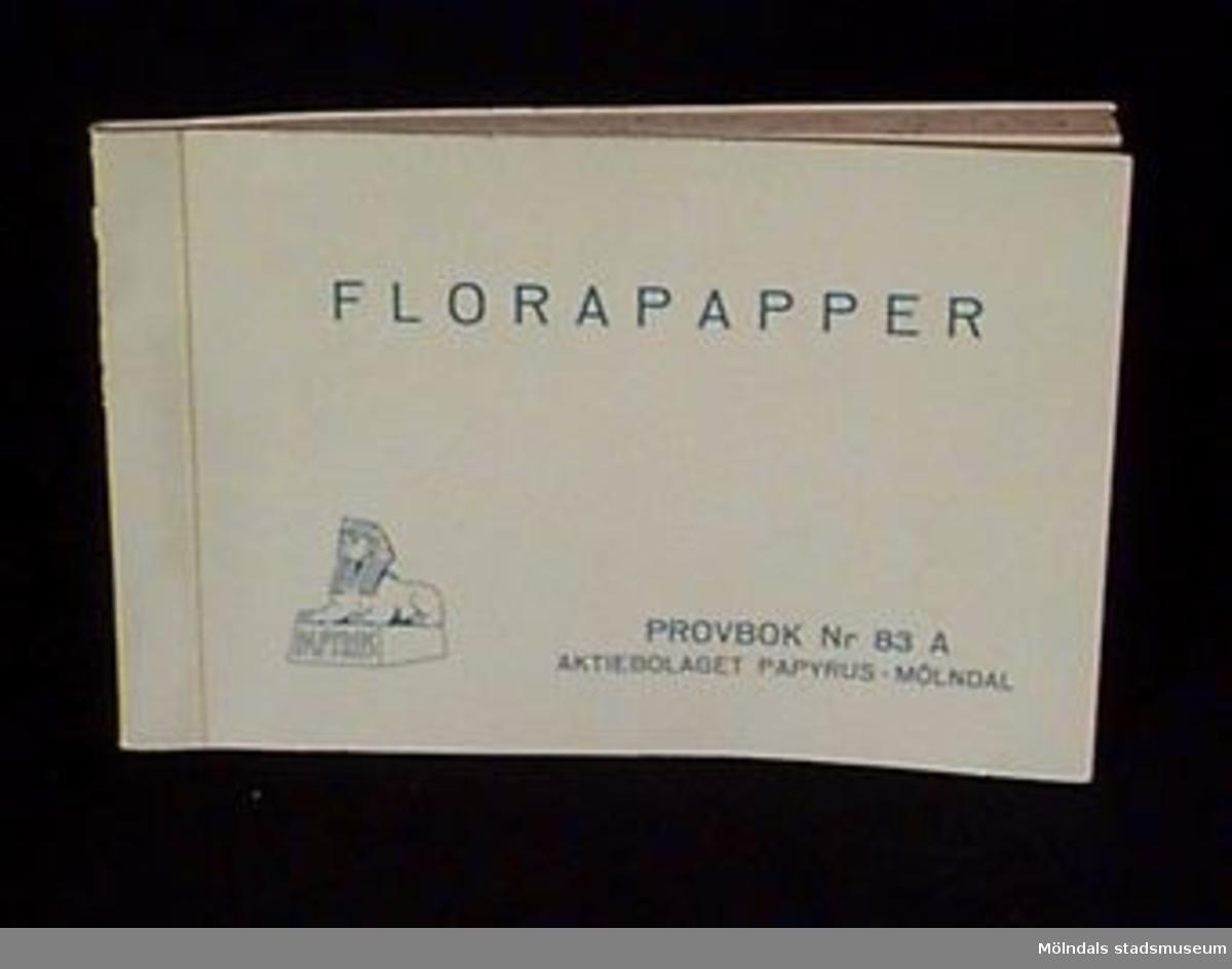 """Häfte med  prover """"FLORAPAPPER PROVBOK Nr 83 A. Logotyp med sfinx på fundament och tillverkarnamnet på framsidan. På ryggen text """" 83 A FLORAPAPPER"""". Pärmen ljusgrön med blått tryck, vit förstasida, produktinformation i blått tryck. Innehåller 26 st olika provark 209 x 320 mm, för blomsterförsäljning. Mönster med blommor, prickar, kronor, franska liljor, meanderliknande slingor och något slags bladmönster.Litteratur: Papyrus 1895-1945, Minnesskrift, Esseltes Göteborgsindustrier AB, Göteborg 1945."""