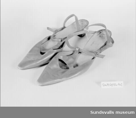 Ett par röda skor med spetsig tå och 4 cm hög klack. Hättan slutar långt fram på foten. Ett triangelformat stycke är fastsytt på två ställen mot hättan. Spetsen mot vristen har en öppning att trä vristremmen genom. Metallspänne. Storlek 7. Otydlig märkning på sulan.