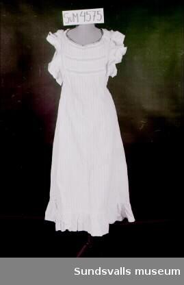 Naturvitt förkläde med bröstlapp tillverkat i bomullstyg. Volang nertill, samt vid ärmhålen. Infällda spetsar på bröstlappen och axelbanden. Knäppning i midjan bak med en knapp.