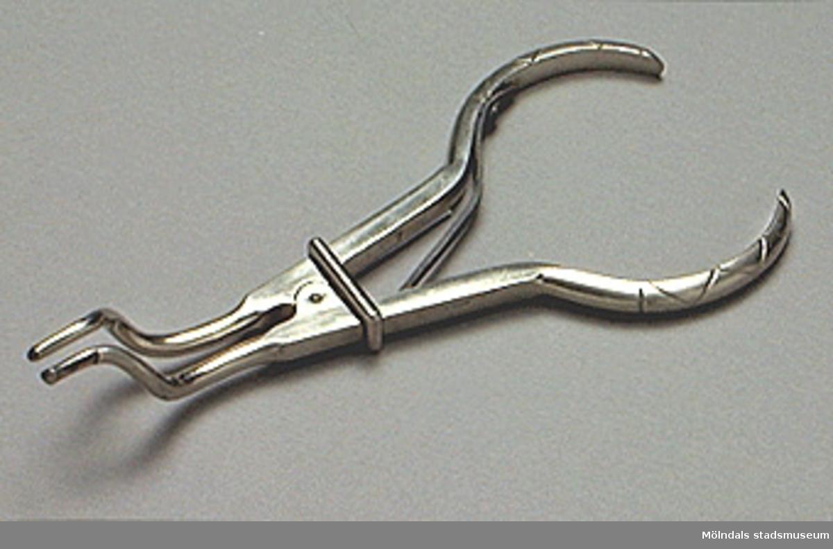 Metalltång, troligen för att vidga näsborrarna med vid undersökningen. Tången är ställbar.