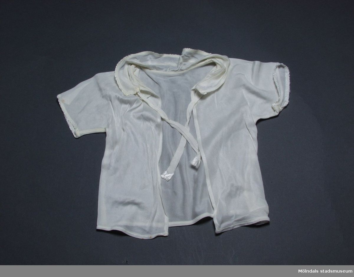 Spädbarnsskjorta i vit charmeuse. Halsrysch och ärmar är kantade med en liten langett.