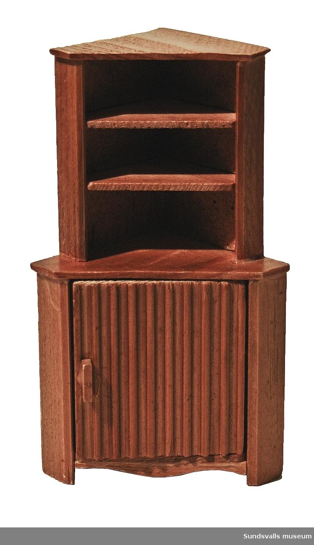 Hörnskåp. Dockskåpsmöbel med bakstycke av spånskiva och resten i brunbetsat trä. Två hyllplan och ett underskåp med ett hyllplan.