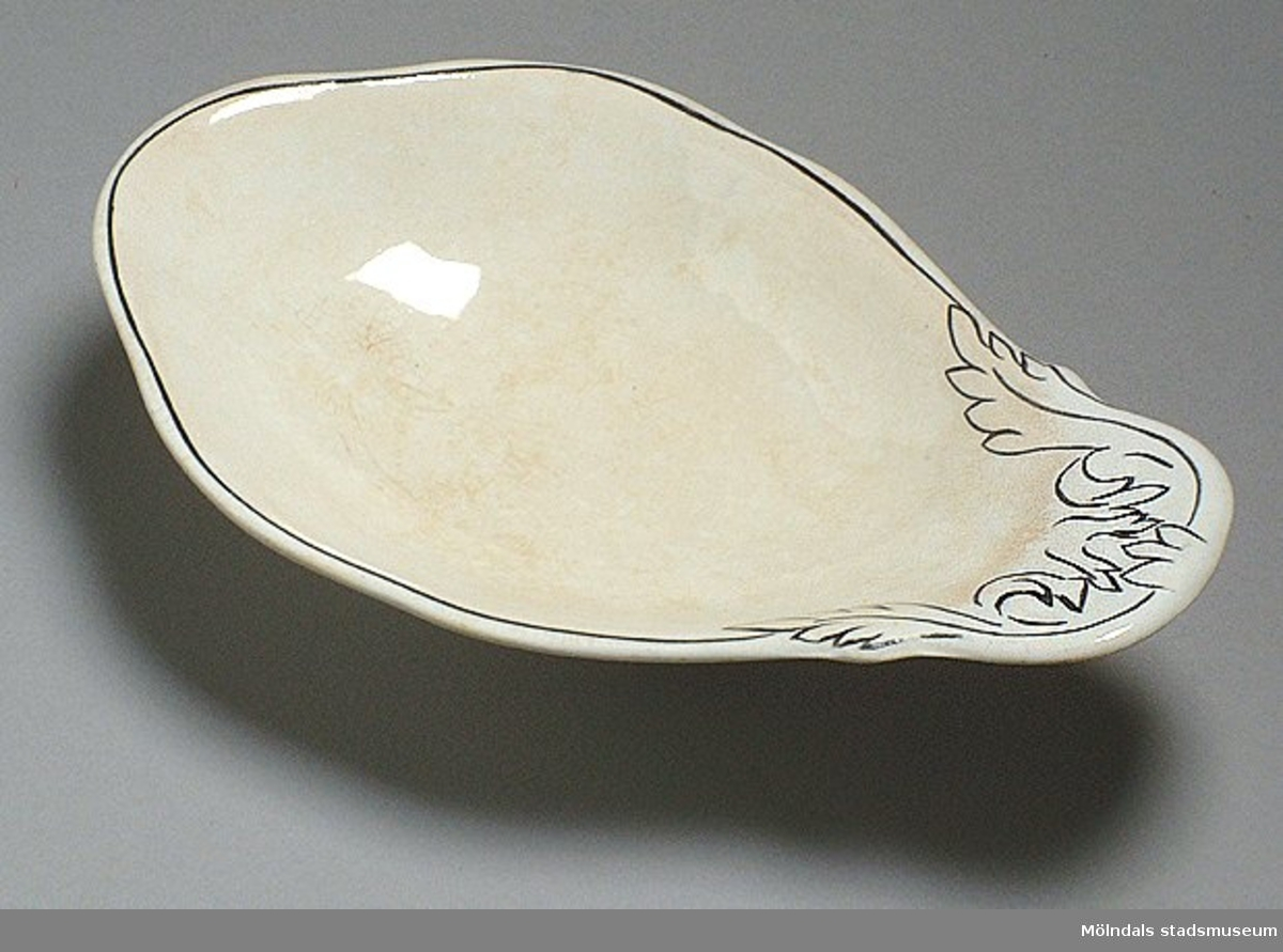 Serveringsfat, vitt med svart kantdekor. Krackelerat. Fatet användes på Mölndals sjukhus, privatavdelningen.