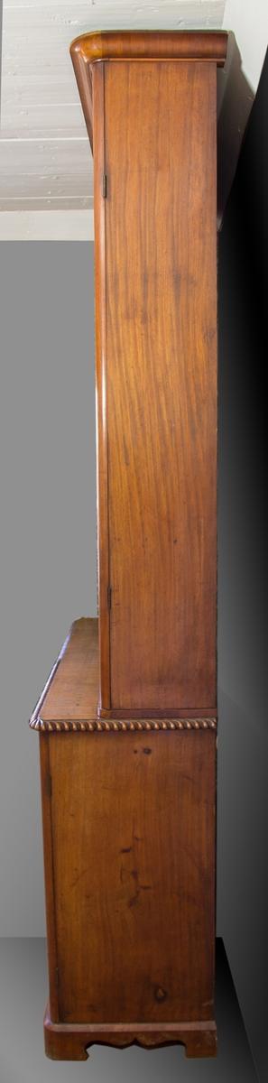 Skåp tillverkat i furu och mahogny. Övre delen utgörs av en vitrindel som är krönt med en profilerad list. Vitrindelens glasdörrar har spröjsverk formade som gotiska bågar. Skåpdelen nedtill har dörrar med speglar och inuti flyttbara hyllplan. Skåpdelens sarg har en skulpterad list. Skåpet vilar på en profilerad sockel.
