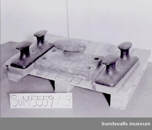 SuM 5559:1-3 tre stycken pollare i gjutjärn, varav två i par monterade på träplatta (49x16 cm), samt en ensam gulmålad (43x29 cm). Pollaren är, monterad på fartygsdäck eller kaj, avsedd som fäste för kablar eller förtöjningstrossar.