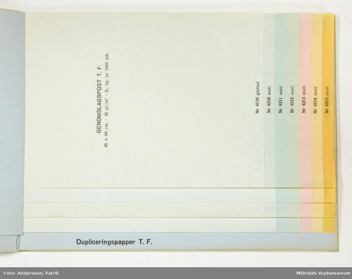 """Häfte med prover, """"Provbok Nr. 13. Genomslagspost och Dupliceringspapper"""". Pärm av grått, grovt papper med svart tryck, Papyrus logotyp med sfinx. Provark i olika storlekar och färger ordnade lättöverskådligt, samt märkta med siffra och produktinformation. Litteratur: Papyrus 1895-1945, Minnesskrift, Esseltes Göteborgsindustrier AB, Göteborg 1945."""