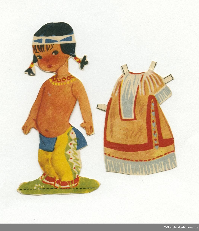 """Pappersdocka med kläder, urklippt ur tidning på 1950-talet. Dockan föreställer en liten indianflicka med svart hår i flätor och pannband, iklädd benkläder, höftskynke och mockasiner. Garderoben består av en klänning, dekorerad och med fransar runt hals, ärm och nederkant. Dockan och kläder förvaras i ett vitt C6-kuvert, märkt """"Indianerna"""", men ursprungligen poststämplat i Åbo, Finland 1953, till familjen. I kuvertet förvaras också ytterligare ett plagg, till en docka som dock saknas (MM 04650)."""