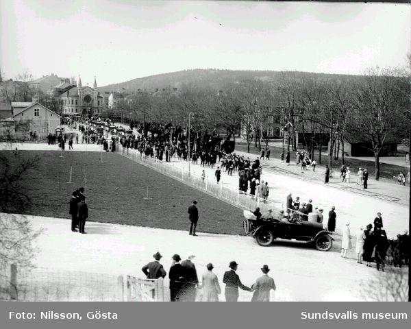 Folksamling med fanor, möjligen på väg till Vindskärsvarv för högtidlighållandet (50-årsminnet) av Sundsvallsstrejken 1879.