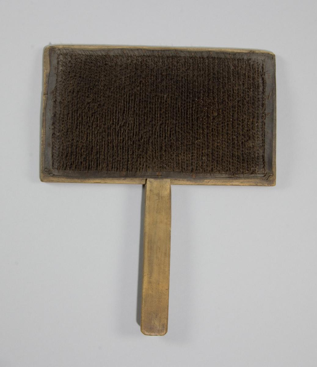 Karda i trä och skinn med piggar av ståltråd. Rektangulär till formen med långt smalt handtag.