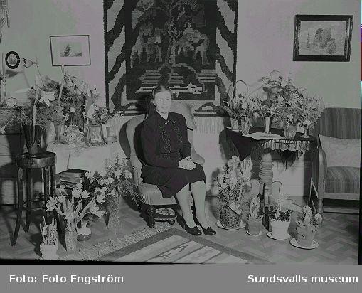 Porträtt, kvinna i rumsmiljö, blommor. Se föregående.