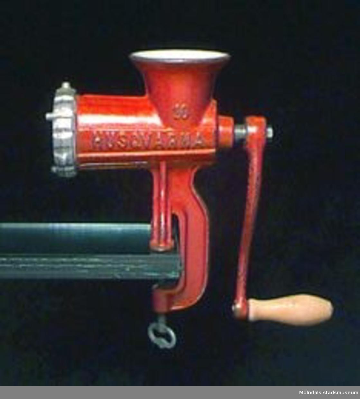 """Rödmålad köttkvarn, """"RELIANCE MADE IN SWEDEN"""", """"HUSQVARNA"""", """"10"""" med guldfärg. Vev med trähandtag. Avtagbar presskiva. Text på presskivan: """"No 10 o 12  4,5"""". På den propellerliknande del som sitter innanför presskivan: """"H"""". Färgen nött.Husqvarna Vapenfabriks AB blev bolag 1867. Fabriken grundades 1689. Tillverkning: bl a vapen, symaskiner, motorcyklar. Hade gjuterirörelse med emaljerings- och förtenningsverk."""