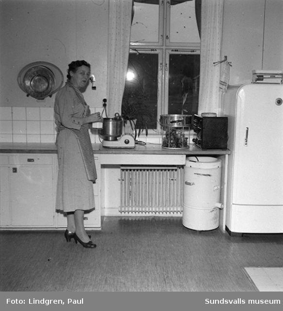 Fru Lindlöf i sitt kök, samt två pojkar som hjälper till med disken.