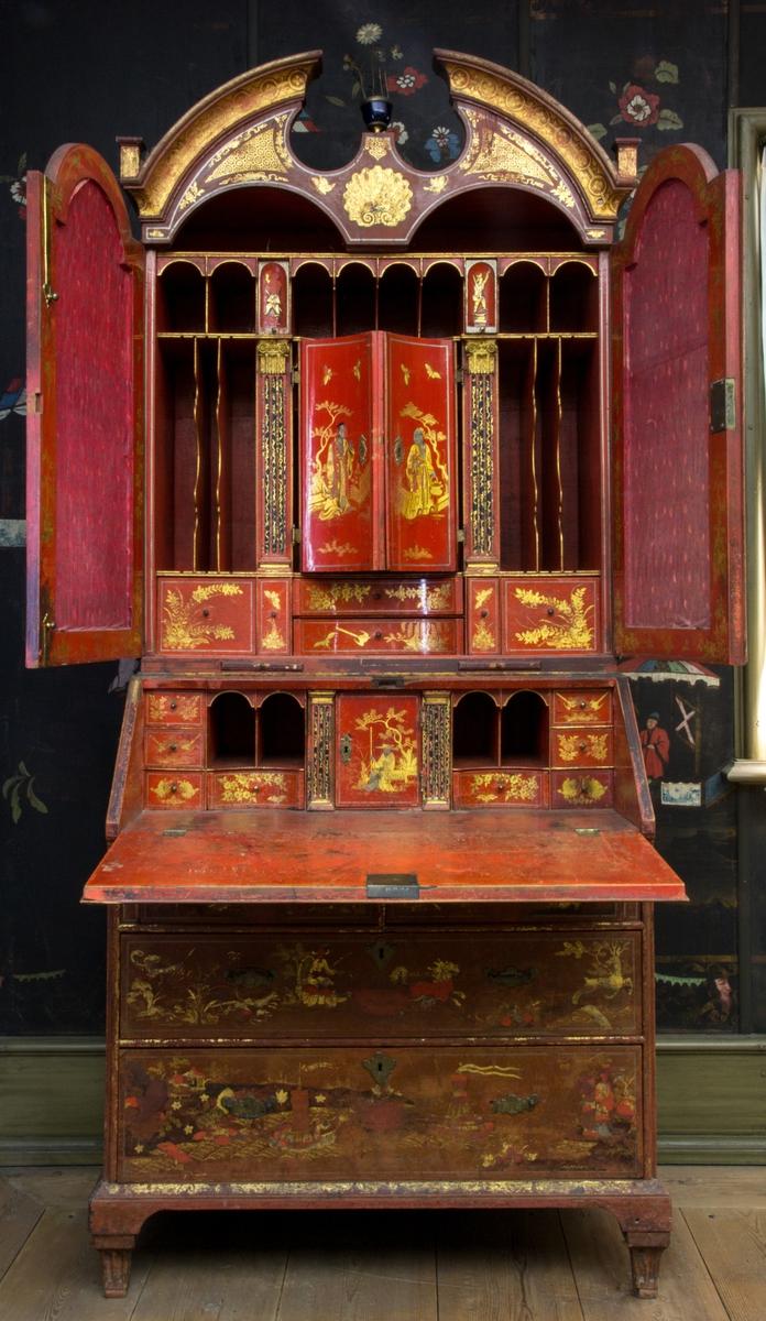 Skrivskåp av engelsk typ, sannolikt i valnöt. Röd till färgen med rik kinesiserande lackmålning i guld och svart. Skåp med runda former, dubbeldörrar med bakomliggande lådinredning. Under detta en snedklaffbyrå i stramare form, samt fyra lådor fördelade på tre lådvarv.