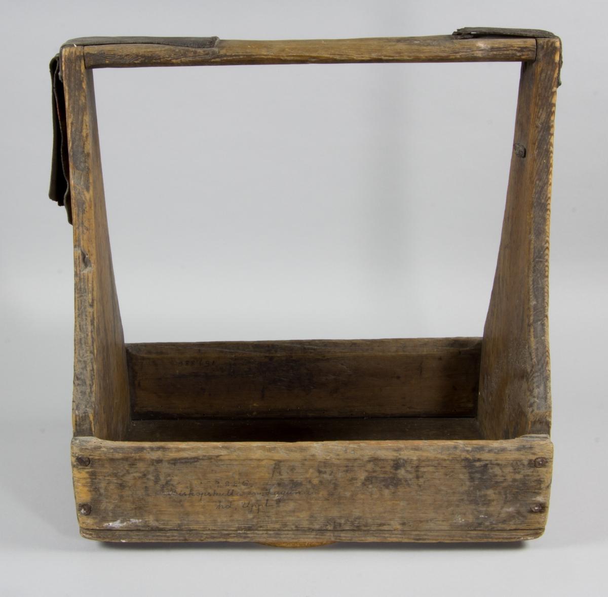 """Knivlåda i trä. Rektangulär med ett fack. Kortsidorna avsmalnande uppåt och med högt handtag. Handtagets hörn med spikade stiglar av läder. Märkt på ena kort sidan: """"AHSn""""."""