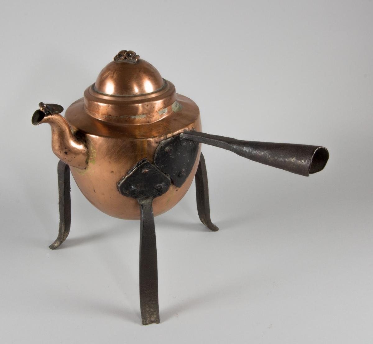 Kaffepanna tillverkad av koppar. Lock med fals som ligger inuti pannan, knopp av rullad plåtbit med runda ojämna kanter. Svängd pip med lövformat lock. Förtent insida. Handtag av järn, bockat för en förlängning av trä. Tre svagt svängda ben av järn med hjärtformade fästen nitade mot pannan.
