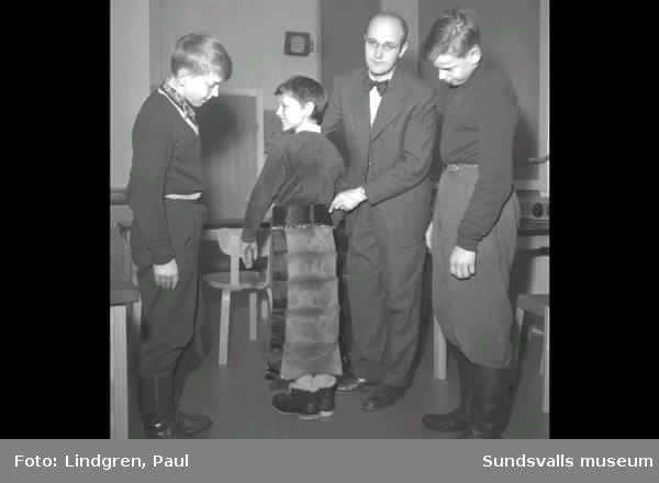 Missionär i Hagaskolan. Pojke provar benkläder.