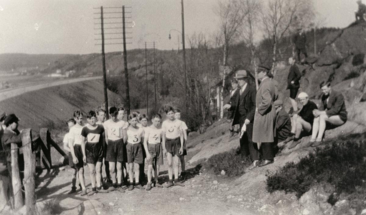 """Pojkar uppställda för terränglöpning i """"Stusshôla"""" (nuvarande Kryssgatan). Lärare med tidtagarur. Åskådare sittandes på berget."""