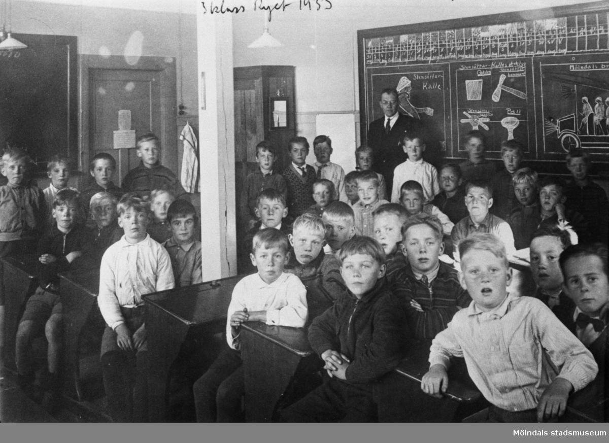 Pojkklass sittande i skolbänkar i klassrum på Ryetskolan. Magister Sven Flodén med elever..