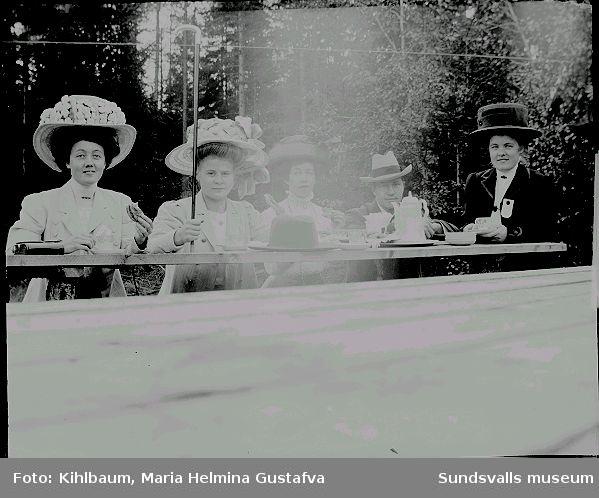 Fyra kvinnor vackra hattar och en man, dricker kaffe utomhus.