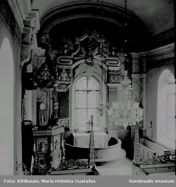Interiör från Tynderö kyrka, präst i predikstol, takkrona, kor.