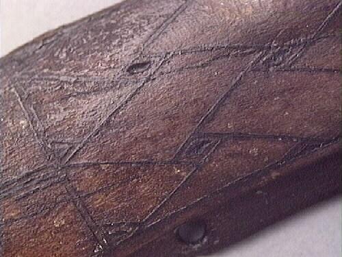 Två stycken väskbyglar. Väskbyglarna är tillverkade i renhorn och utgör tillsammans ett par. Byglarna är bågformade samt försedda med ett hål i vardera ände. Utmed de nedre långsidorna finns fyra mindre hål; den ena bygeln har endast fragmentariska hål medan den andra bygeln har två fragmentariska och två runda hål. Byglarnas ovansidor är svagt bukiga och dekorerade med ett ristat flätbandsmönster. De kvadratiska mellanrummen i flätbanden är försedda med rombliknande utfyllningar. Byglarnas baksidor är släta. Byglarna är relativt välbevarade. Byglarnas färg är gråsvart, vilket är en missfärgning.