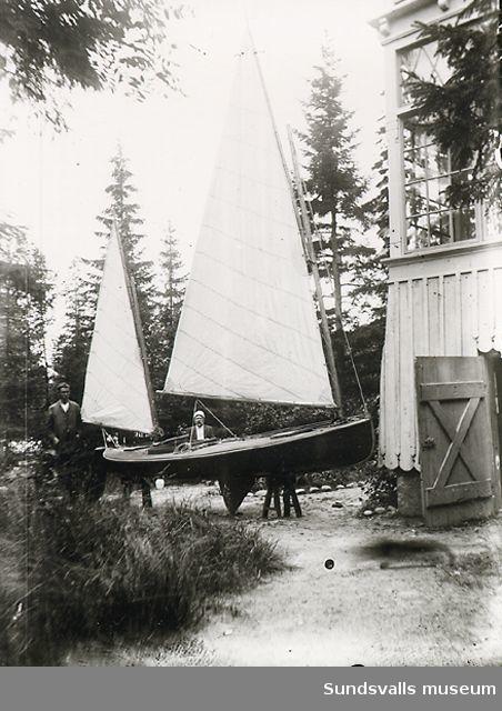 Två män vid en segelbåt som står på tomten.