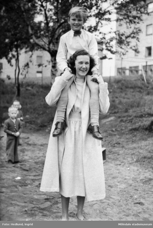 Guldheden 1945-. En pojke sitter på axlarna på en fröken.