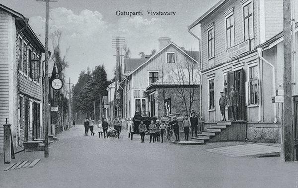Gatuparti från Vivstavarv, till vänster ett bageri och till höger Handelsföreningens butik. Vuxna och barn på gatan och trappan till byggnad. Vykort.