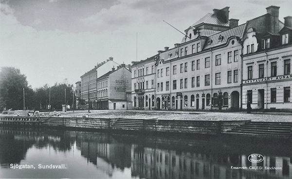 """Till vänster Selångersån till höger Sjögatan med bebyggelse. På fastigheten längst till höger syns texten """"Restaurant Runan"""". Bildtext på vykort """"Sjögatan, Sundsvall""""."""