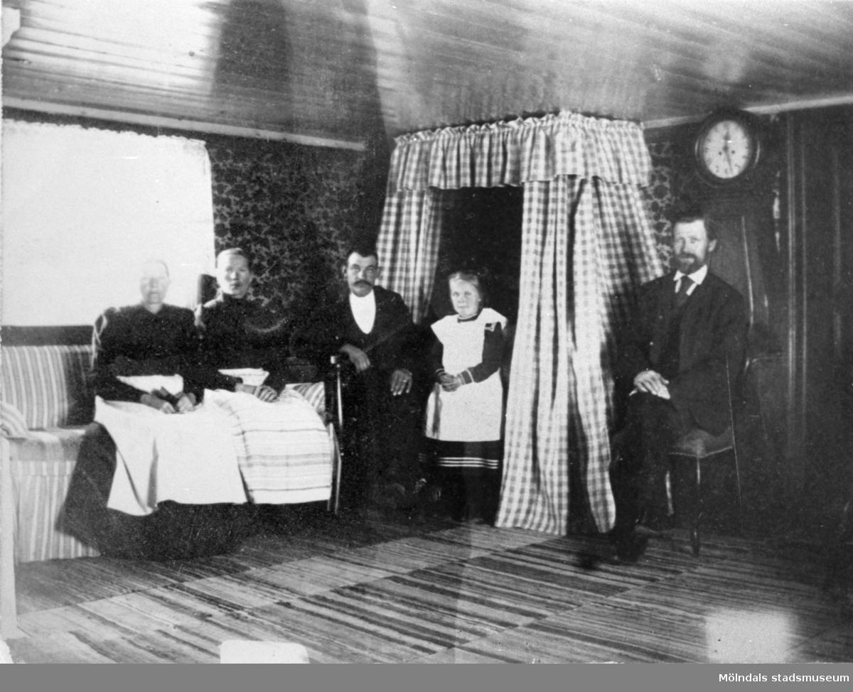 Interiörbild från Lilla Vommedal, 1900-tal. Från v: Maria Eriksson, Anna Carlson. Flickan heter Ulla. Männen Anton och Karl. Anna arbetade som piga hos Maria.