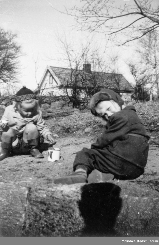 Marie-Louise Lindholm (gift Carlsson) och Lisbeth leker med spade och mugg i trädgården. Flickorna leker på Görjekullen (längst upp på nuvarande Åldermansgatan). I bakgrunden ses Roten K 18, 1950-tal.