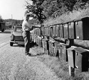 Bilåkande lantbrevbäraren Erik Johansson på linjen Åkersberga-Singö-Björnhuvud-Åkersberga. Brevlådesamlingen vid Singö handel.  Foton augusti 1961.