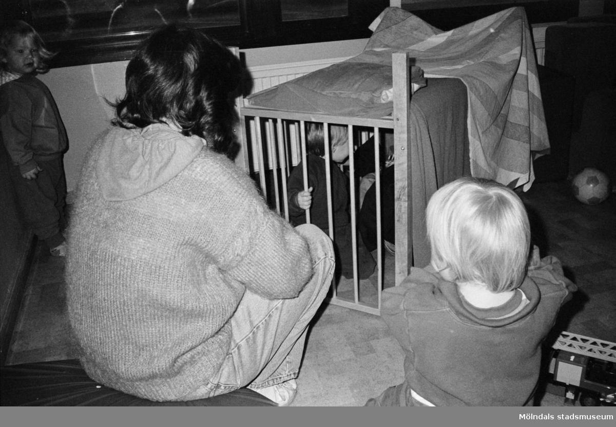 """En förskollärare vid Katrinebergs daghem, hjälper barnen att bygga koja inomhus med hjälp av filtar liggandes över en spjälsäng. Två barn sitter utanför och två barn sitter i """"kojan"""". I bakgrunden ser man en fotboll."""