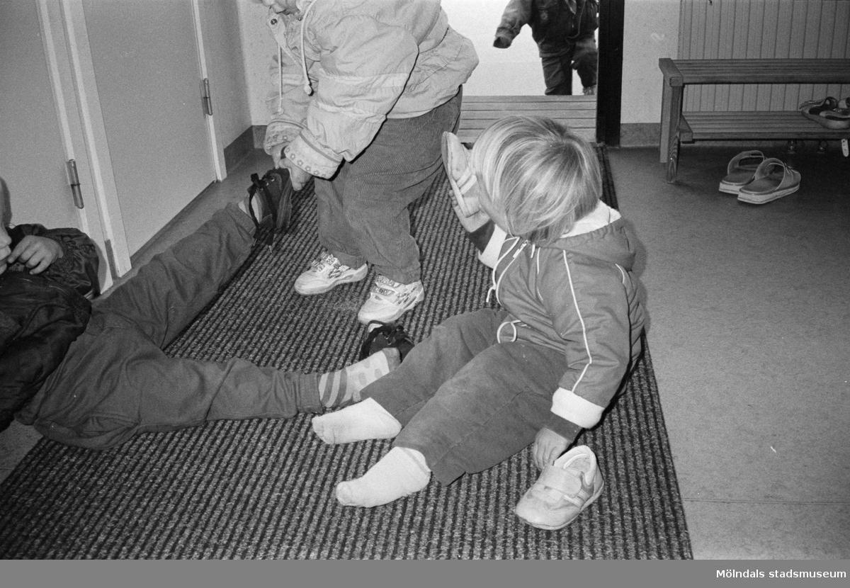 Tre små barn sitter/står på entrémattan och hjälps åt med av-/påklädning av ytterkläder. Katrinebergs daghem.
