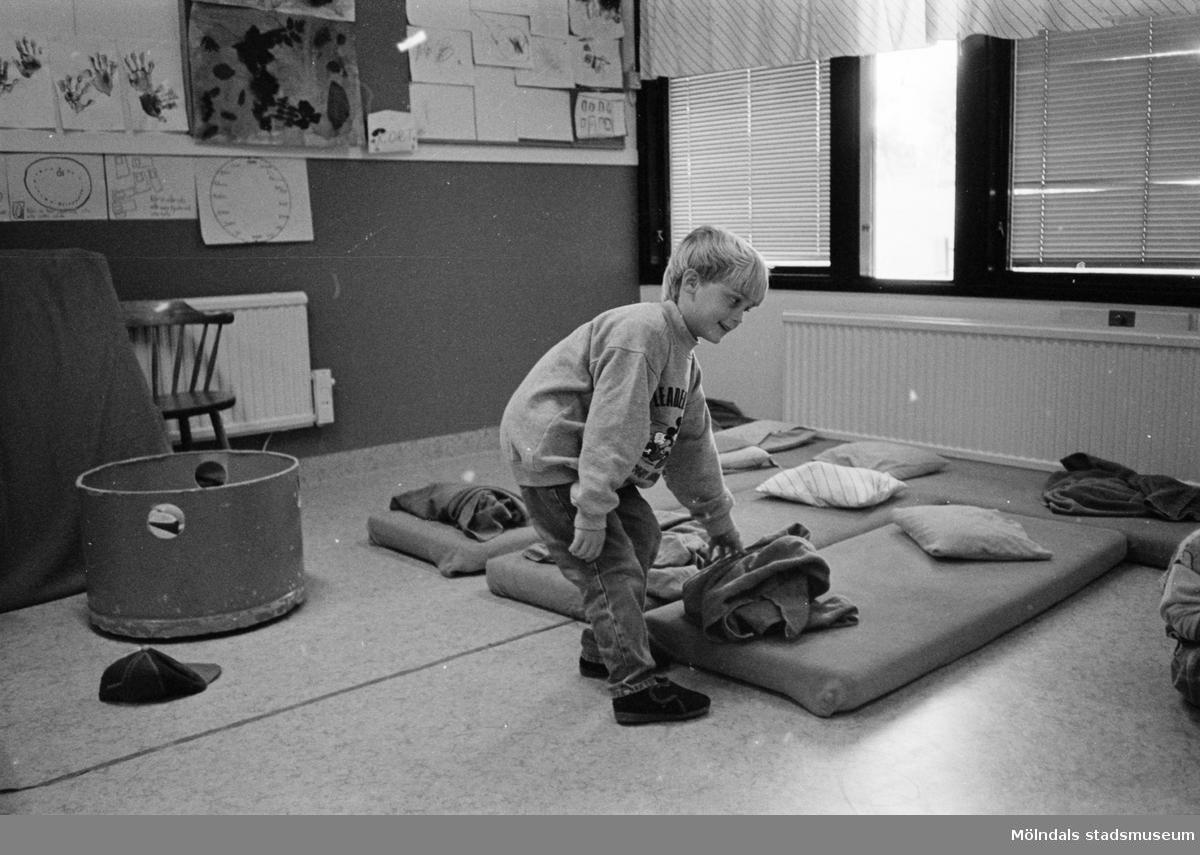 En pojke lutar sig ned och håller på en filt som ligger på en madrass på golvet. På madrassen ligger en kudde. Kanske dags för en liten sovstund? Katrinebergs daghem, 1992.