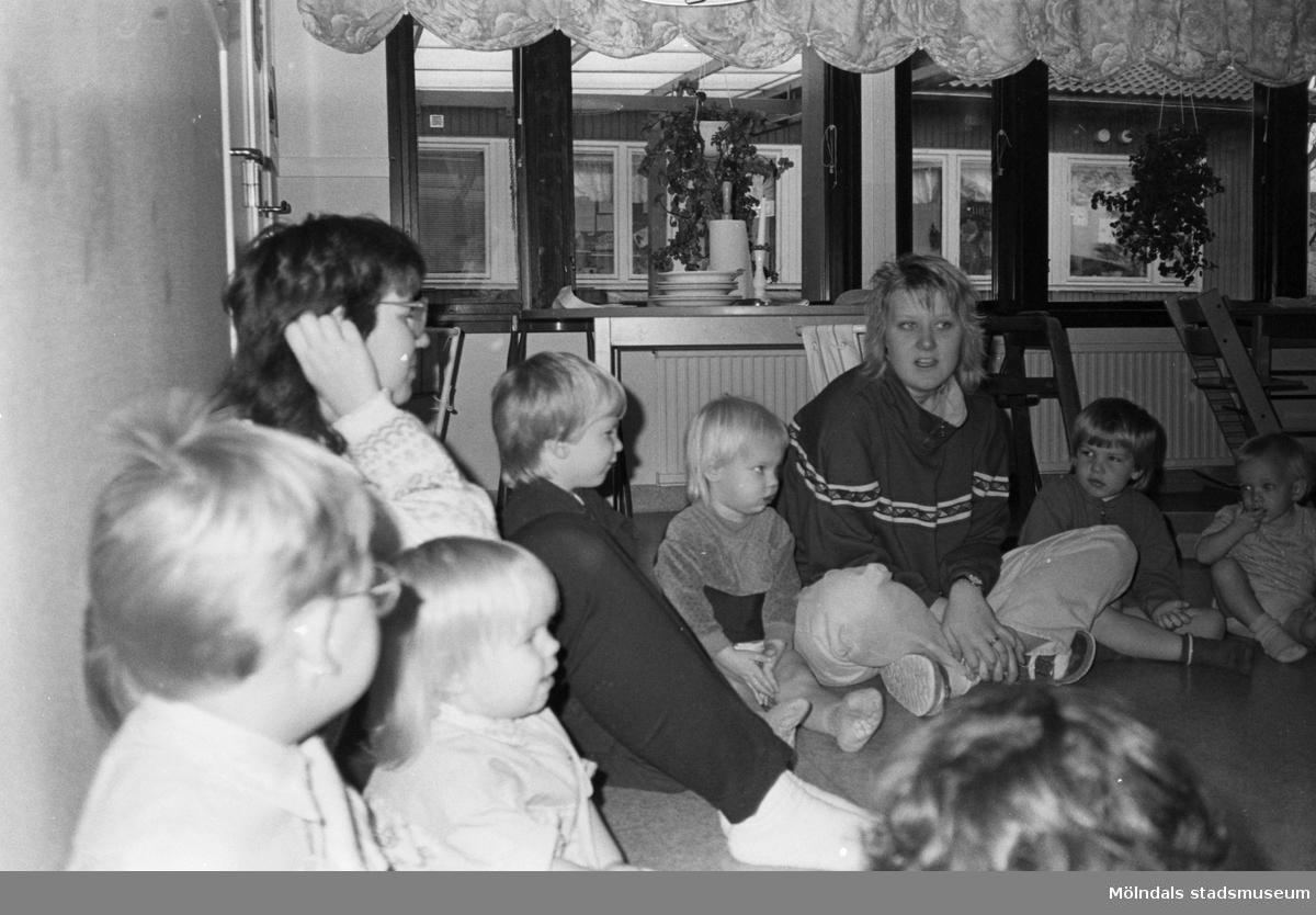 Två förskollärare och flertalet småbarn sitter tillsammans i en cirkel på golvet. Utanför rummets fönster kan man se en annan närliggande byggnad. Katrinebergs daghem, 1992.